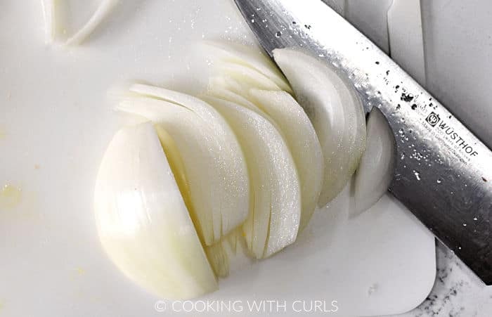 Onion half sliced into thin strips with a chefs knife.