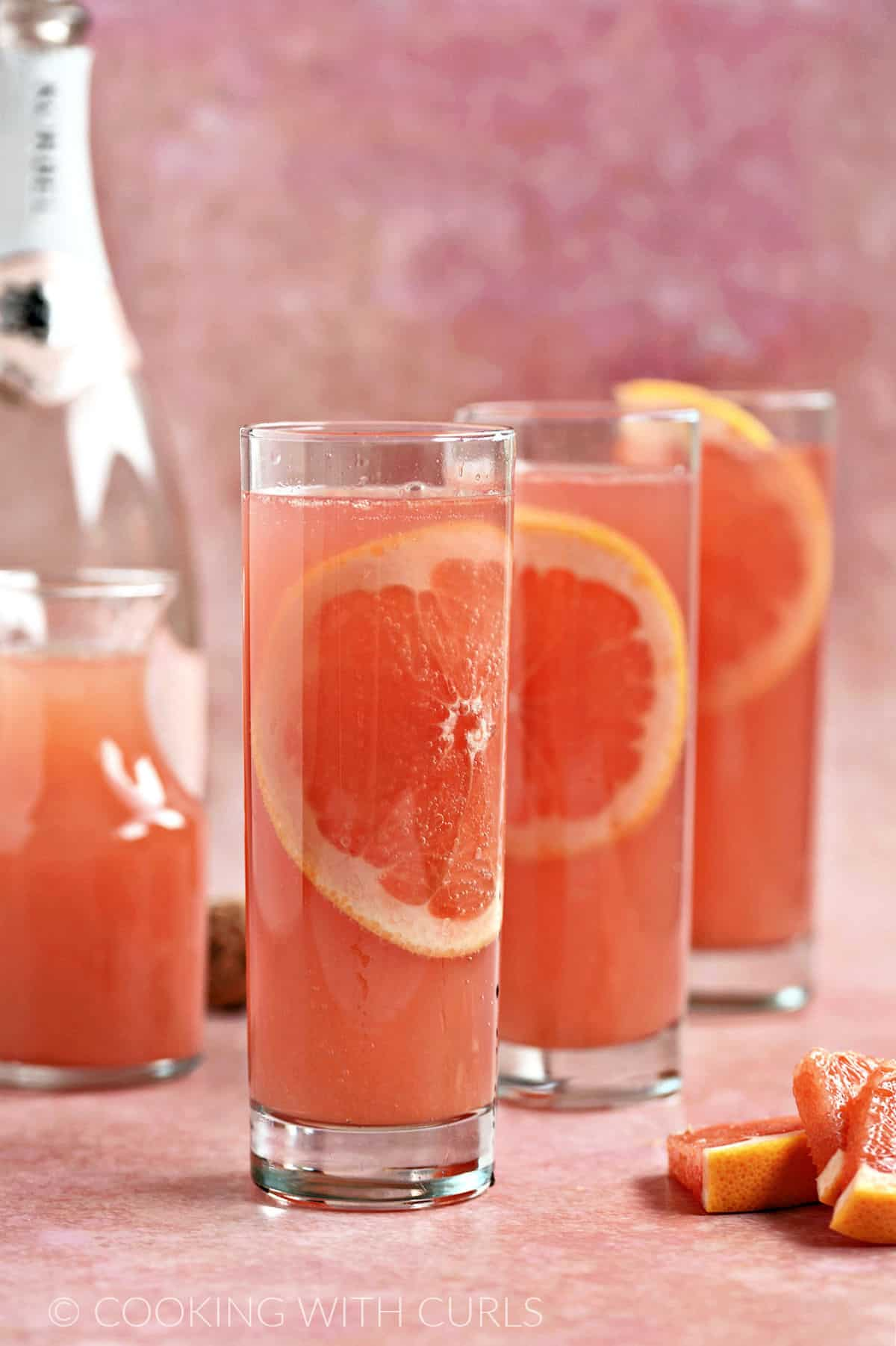 Three skinny glasses filled with a thin slice of grapefruit, sparkling wine and red grapefruit juice with a carafe of grapefruit juice in the background.