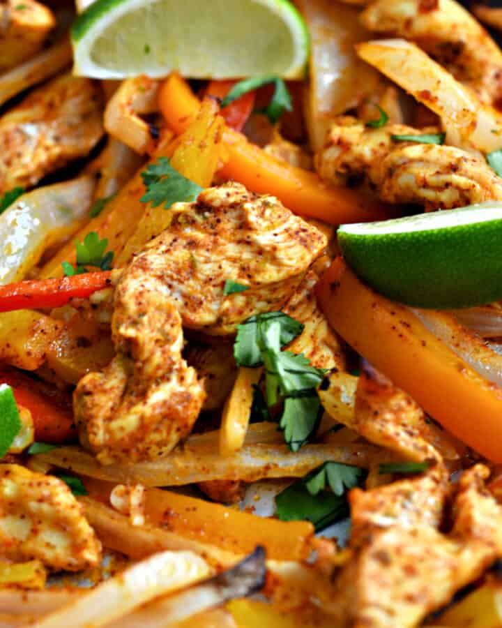 Strips of chicken, onion, red, orange and yellow bell peppers, and lime wedges.