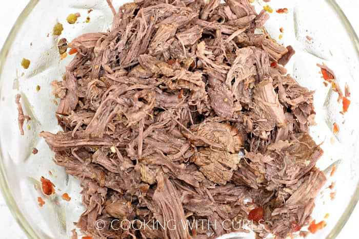 Shredded beef in a glass bowl.