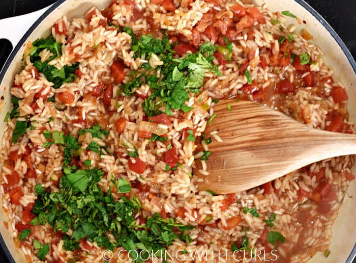 Stirring cilantro into the Mexican rice with a wooden spoon.