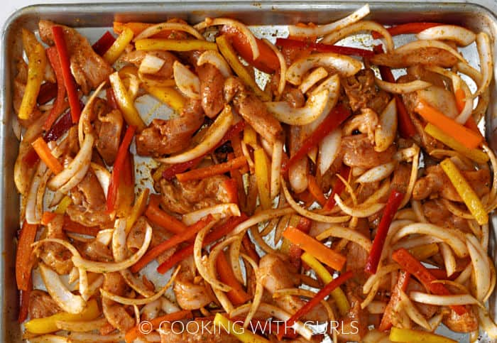 Strips of marinade covered chicken, onion, red, orange and yellow bell peppers on a sheet pan.