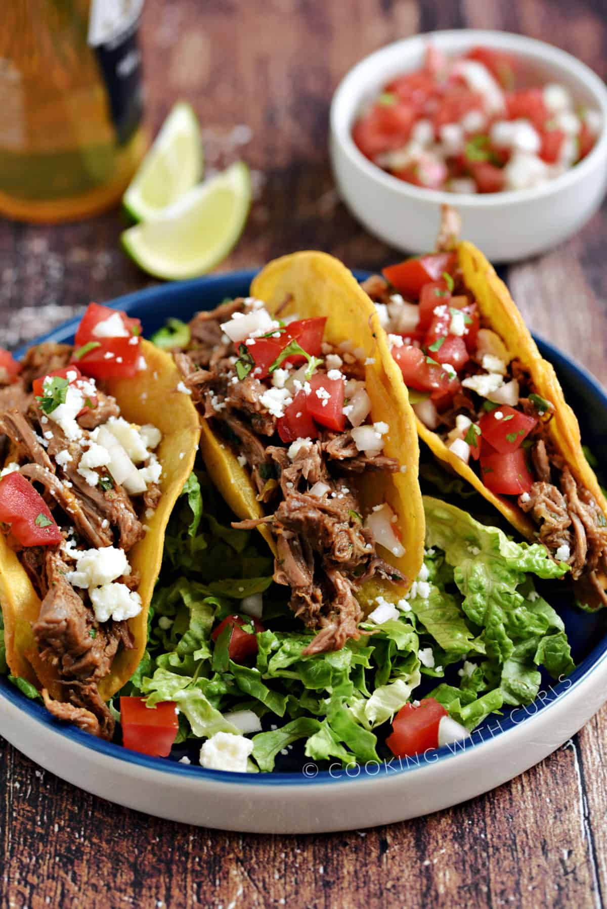 Three Mexican Shredded Beef hard-shell tacos on a bed of shredded lettuce with a bowl of pico, a bottle of beer and two lime wedges in the background.