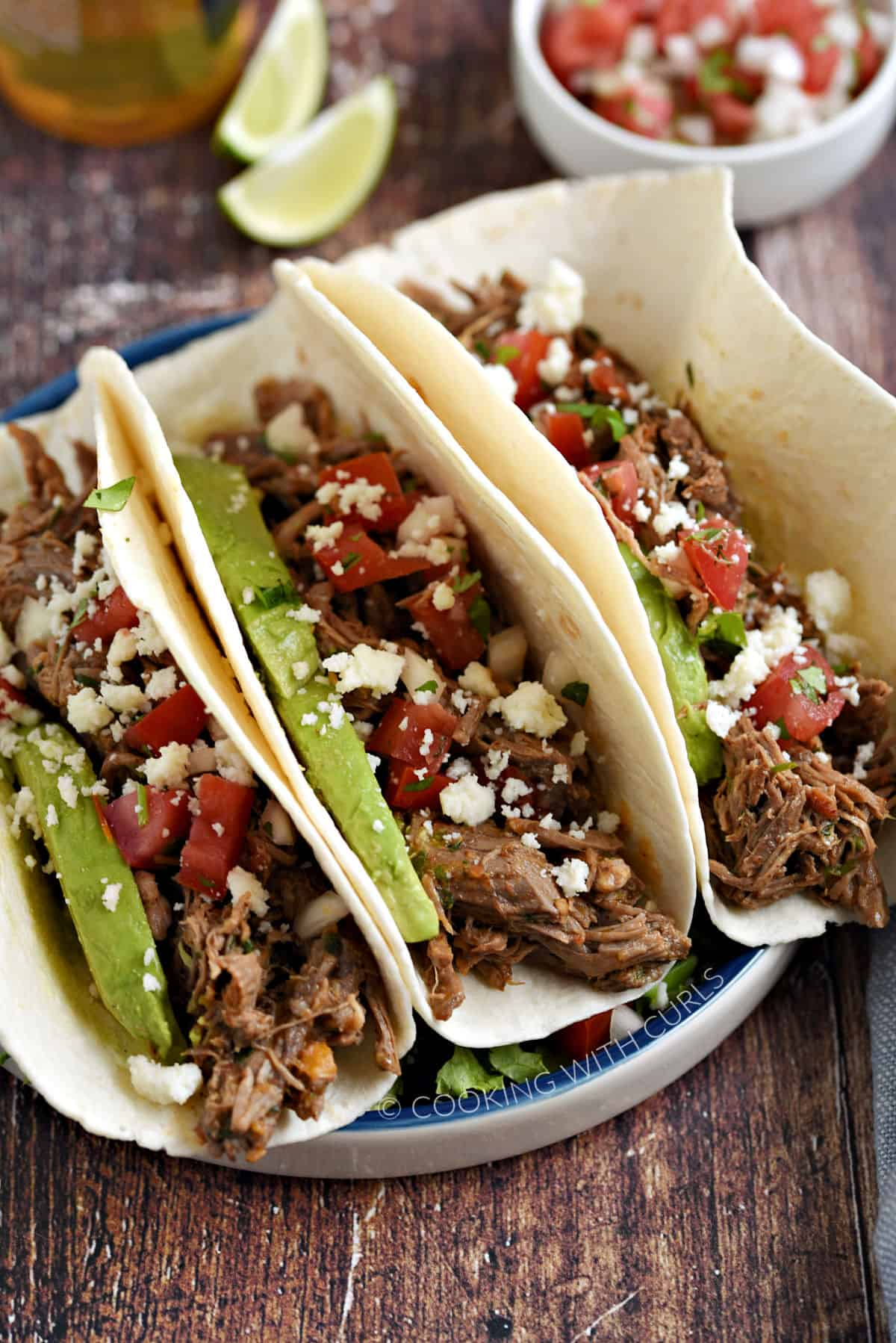 Three Mexican Shredded Beef soft tacos topped with crumbled queso, diced tomatoes and onion, and avocado slices with a bowl of pico and two limes in the background.