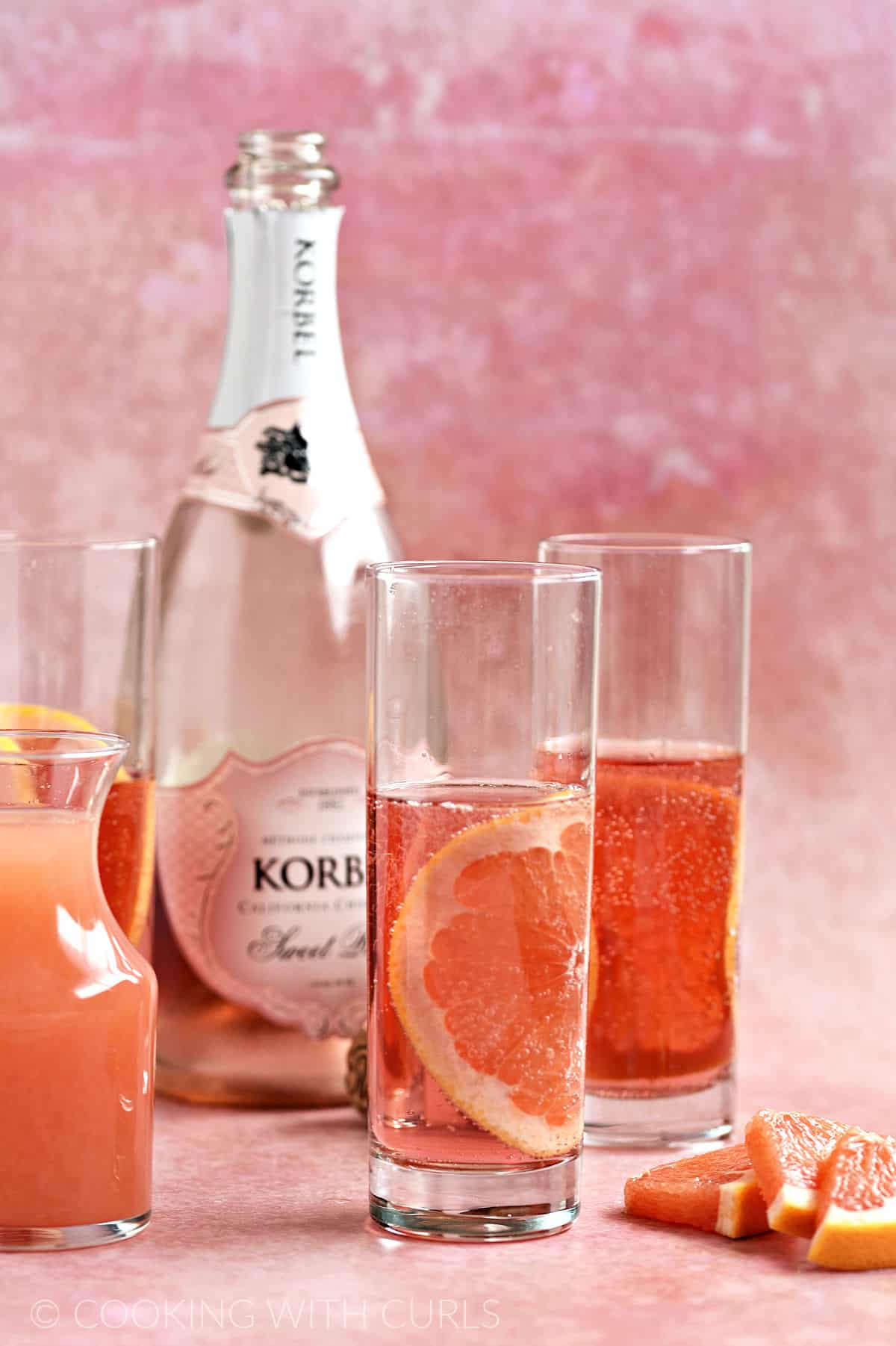 Three skinny glasses filled with rose champagne and a grapefruit slice with a bottle of champagne and carafe of grapefruit juice in the background.