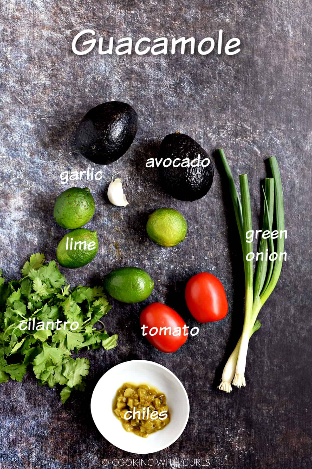 Two avocados, limes cilantro, garlic, green onions, tomatoes, and chiles.