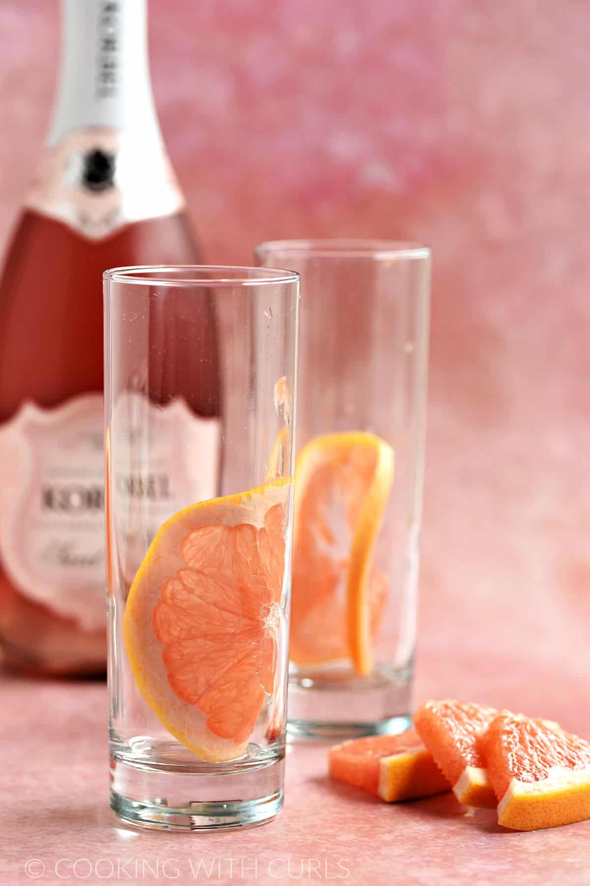 Two skinny glasses with a slice of red grapefruit in front of a bottle of pink sparkling wine and three grapefruit wedges on the right side.