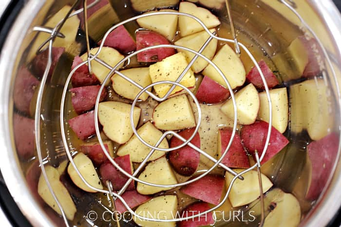 A wired rack laying on top of chicken stock, quartered red potatoes, butter, salt and pepper.