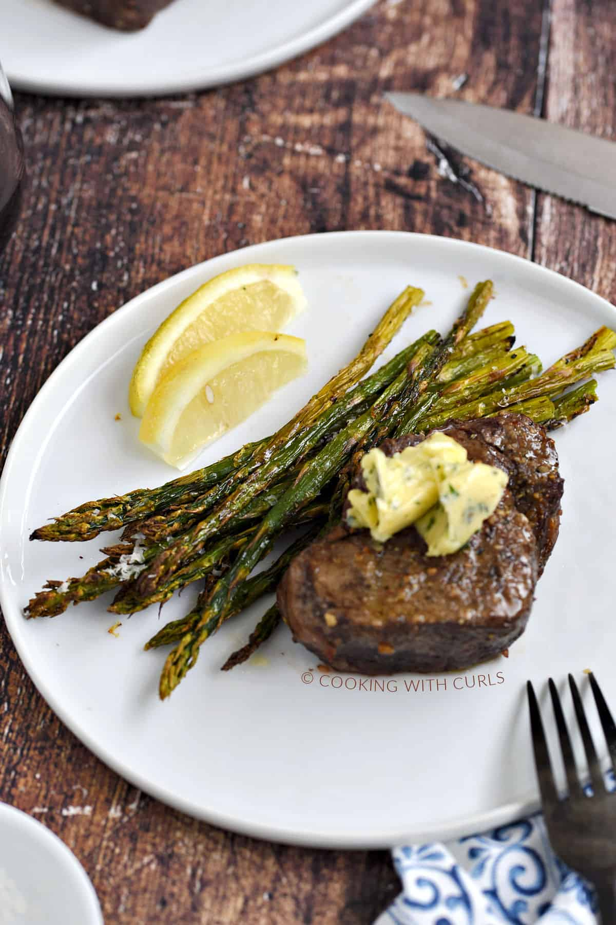 Air Fryer Steak and Asparagus topped with garlic butter and lemon wedges on a white plate.