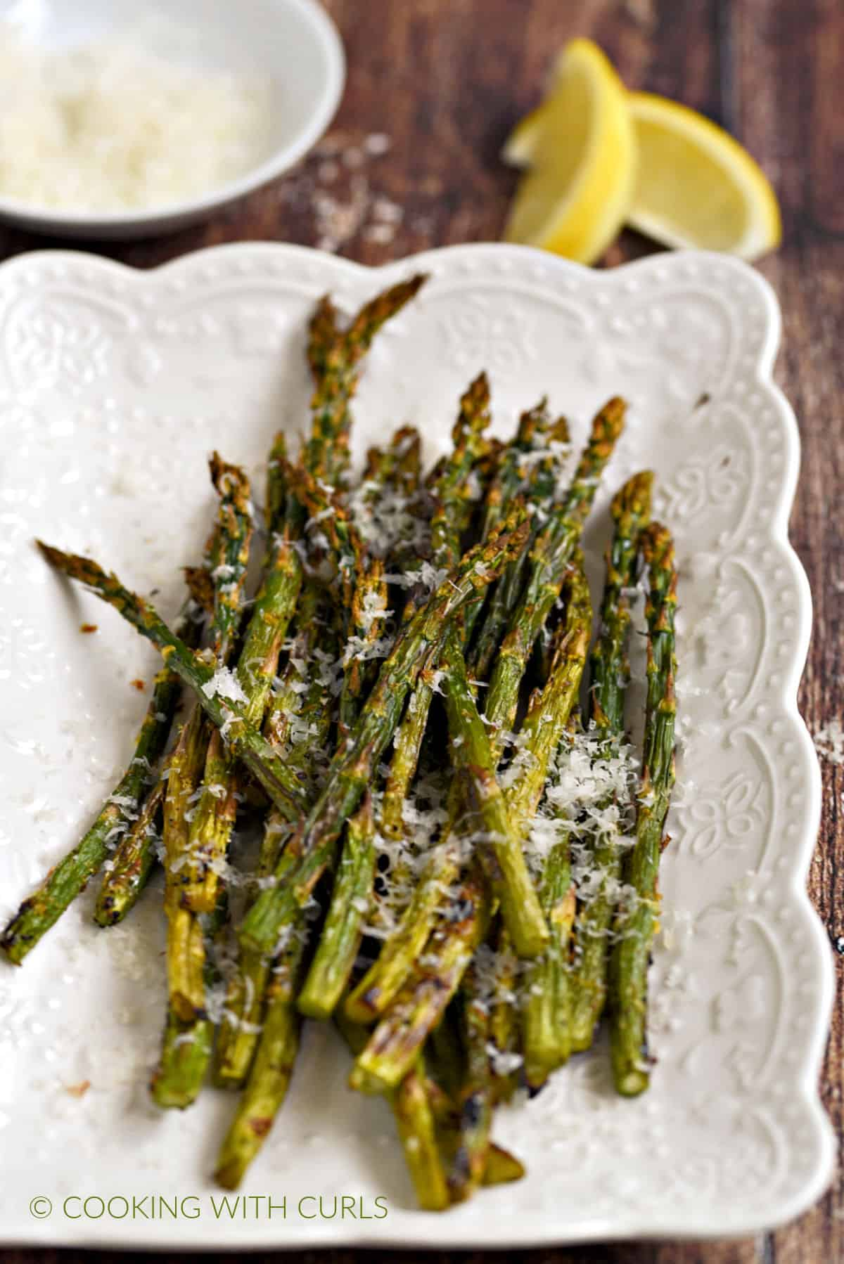 Asparagus spears topped with parmesan cheese and lemon zest on a white platter with a bowl of cheese and two lemon wedges in the background.