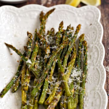 Asparagus spears topped with lemon zest and parmesan cheese laying on a white platter.