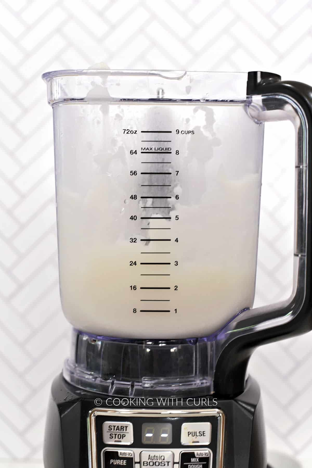 Coconut milk, cream, rum, and pineapple juice blended together in a blender.