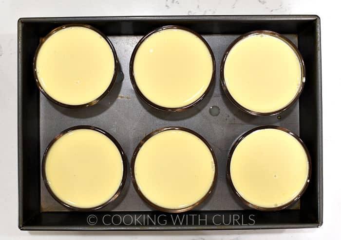 Custard mixture poured into six caramel lined custard cups in a baking pan.