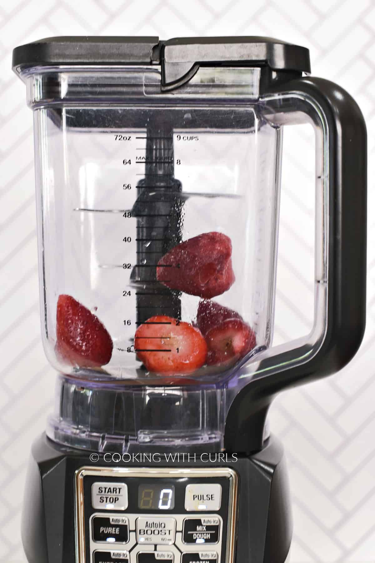 Frozen strawberries, rum, and pineapple juice in a blender.