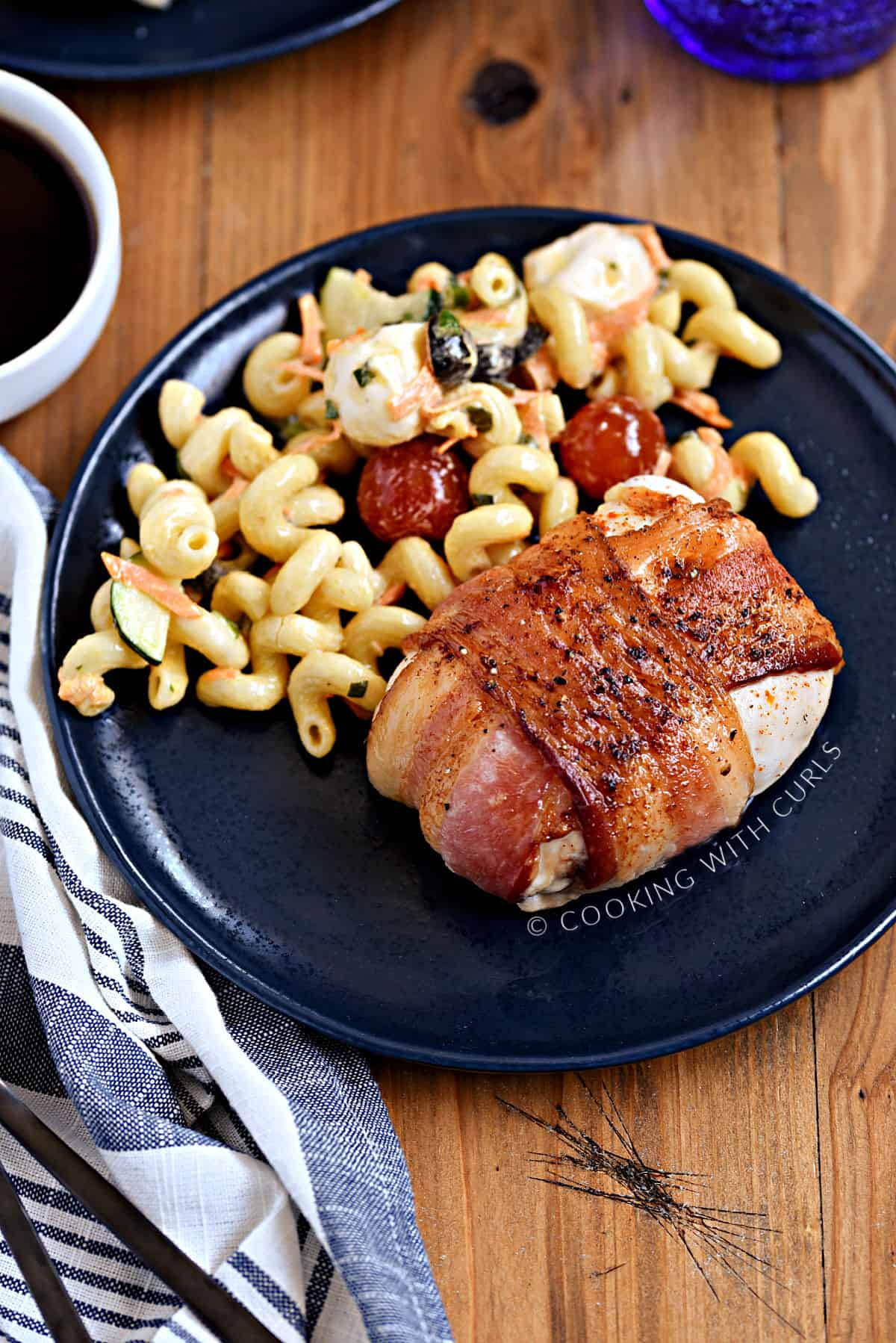 Bacon wrapped chicken and pasta salad on a blue plate.