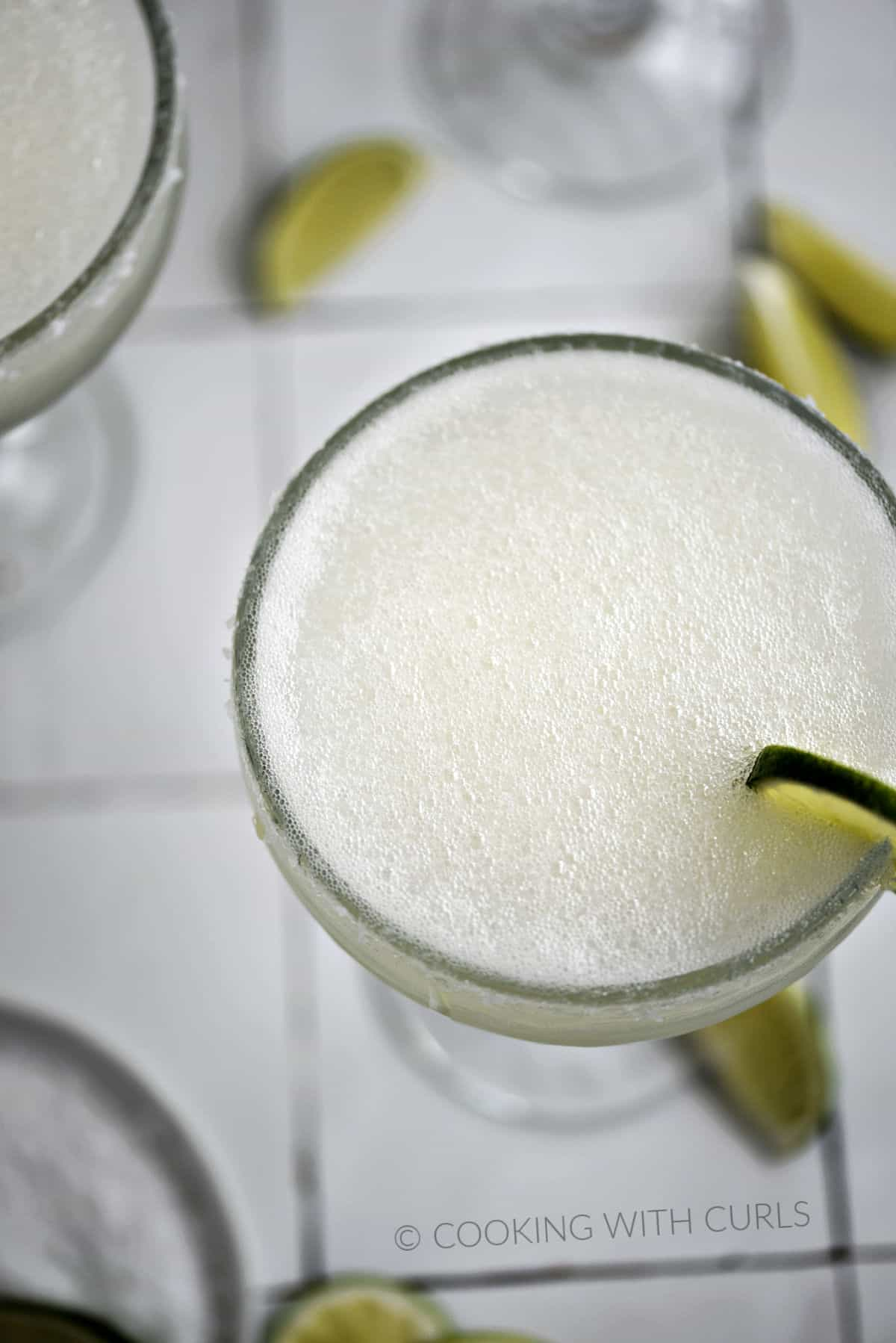 Looking down on a frothy frozen cocktail in a salt-rimmed margarita glass with a lime wheel garnish.