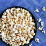 A bowl of popcorn on a blue tile background with title graphic across the top.