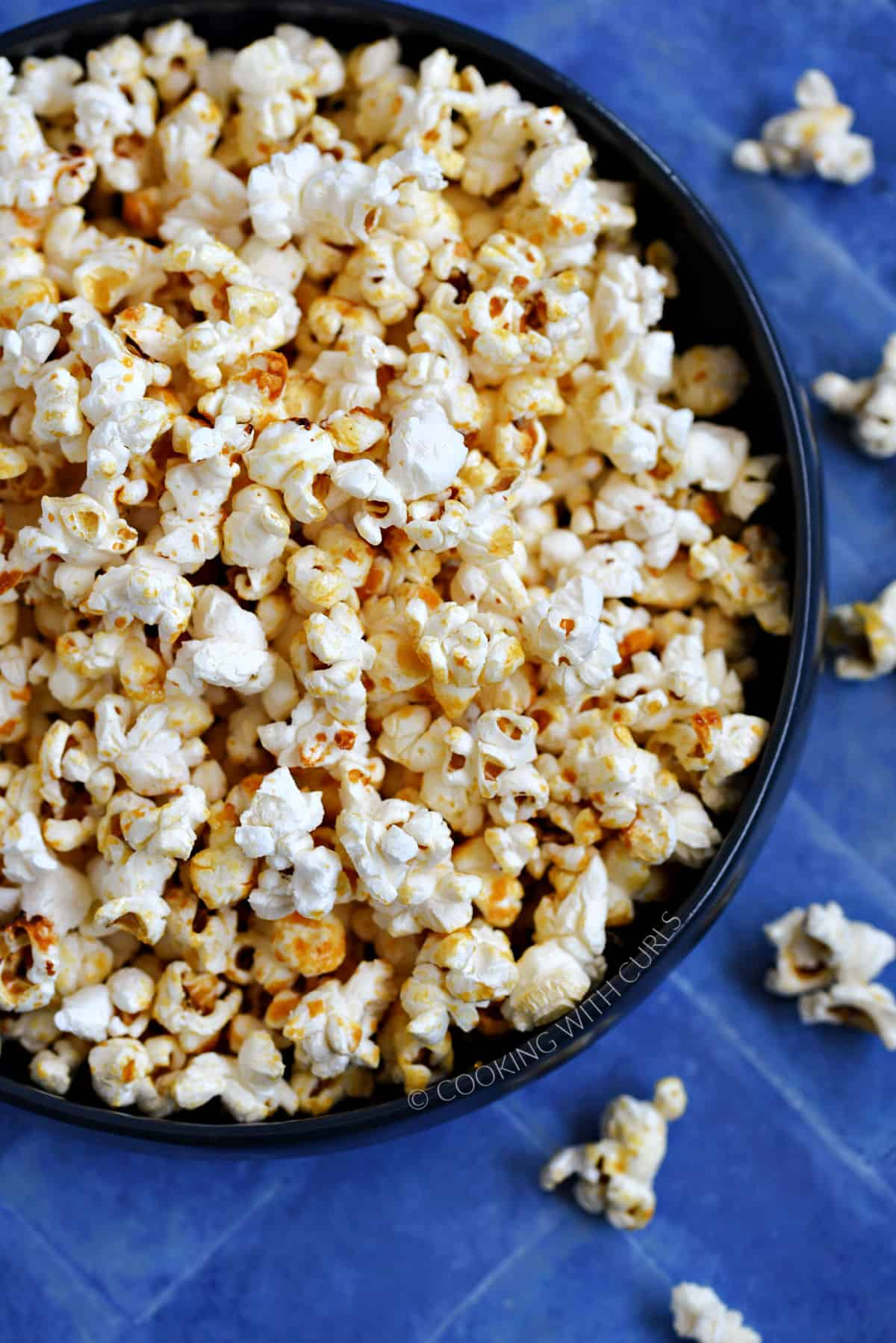 A close-up image of a bowl full of kettle corn popcorn sitting on a blue tile background.