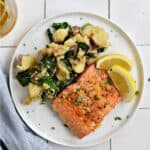 A salmon filet and mashed potatoes mixed with spinach on a white plate with two lemon wedges with title graphic across the top.