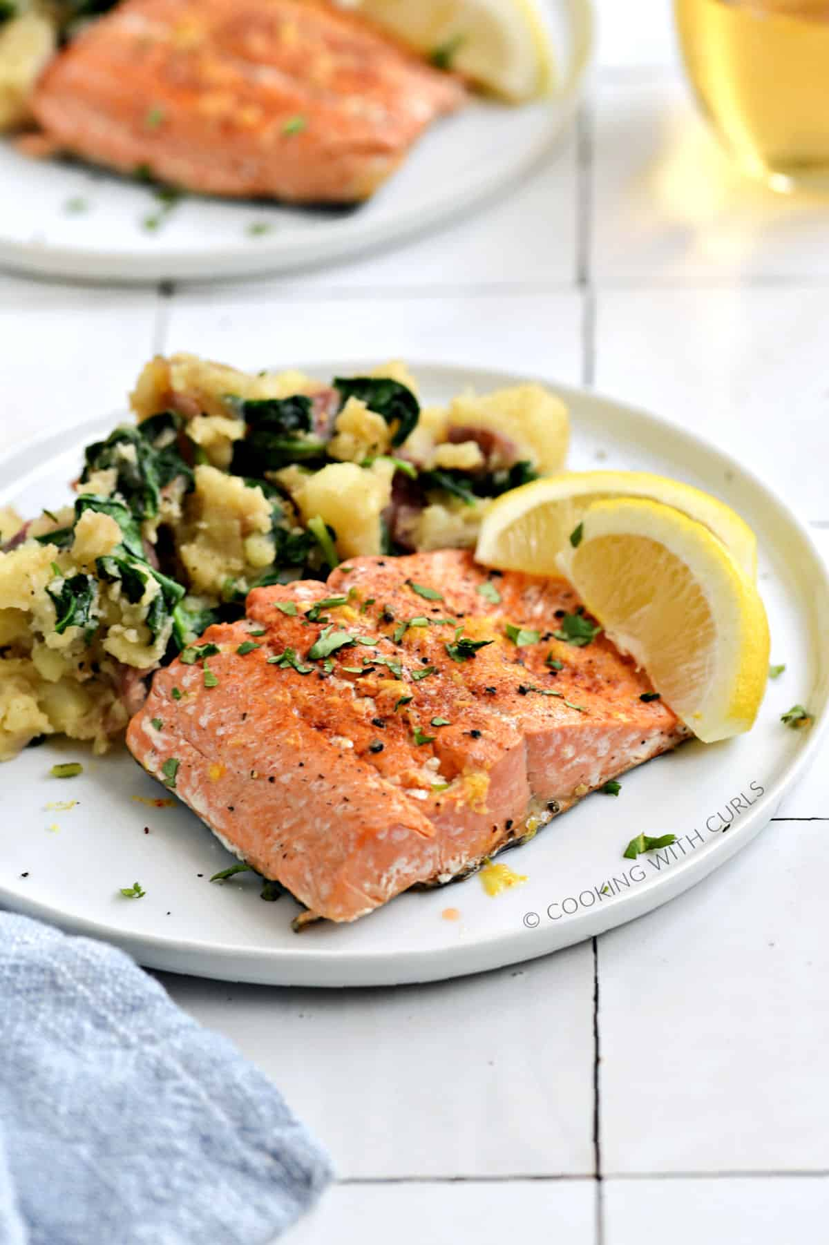 A salmon filet and mashed potatoes mixed with baby spinach on a white plate with two lemon wedges.