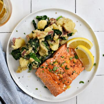 A salmon filet and mashed potatoes mixed with spinach on a white plate with two lemon wedges.