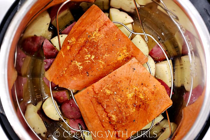 Looking down on two salmon filets on a wire rack over quartered red potatoes and chicken stock inside a pressure cooker.