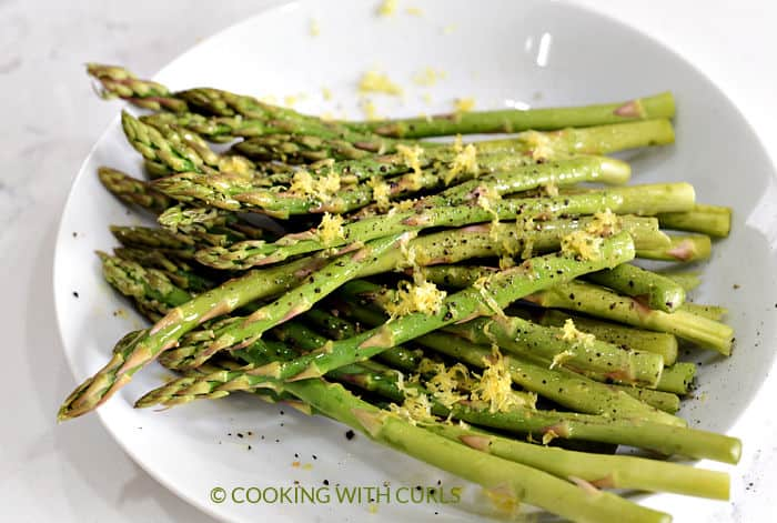 Raw asparagus tossed with oil, lemon zest and pepper in a white bowl.