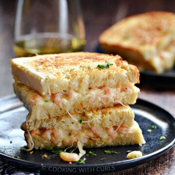 Two halves of a shrimp grilled cheese stacked on top of each other on a blue plate with a second sandwich and glass of white wine in the background.