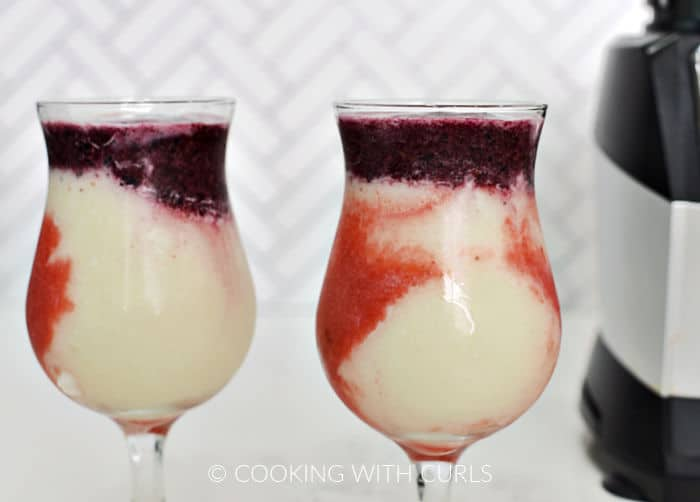 Strawberry, white pina colada, and blueberry layers in shaped glasses.