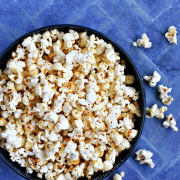 instant pot kettle corn in a blue bowl on a blue background.