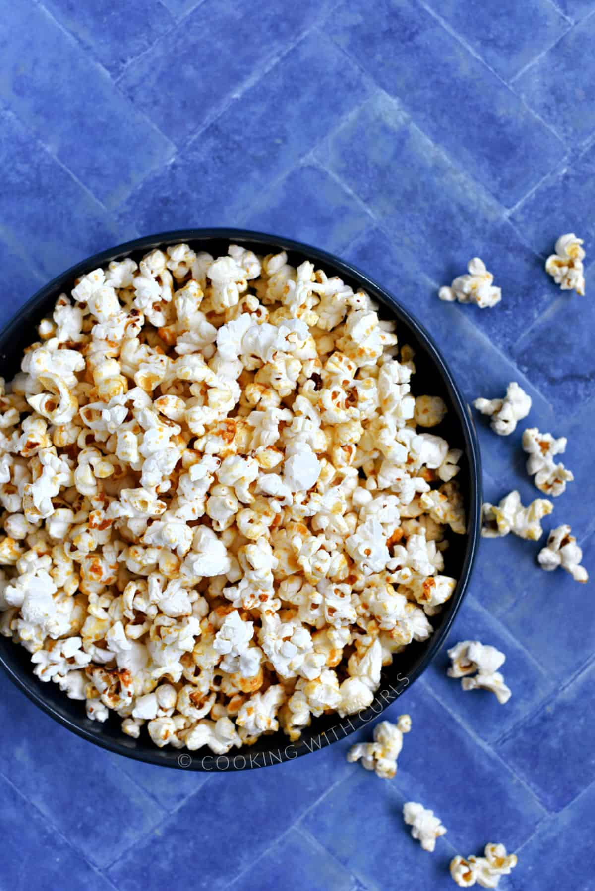 A bowl full of kettle corn popcorn sitting on a blue tile background.