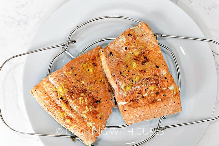 Two cooked salmon filets on a wire trivet sitting  on a white plate.