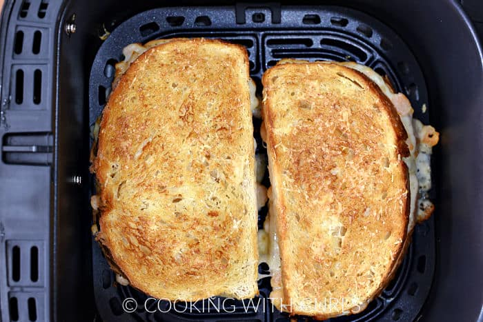 Two shrimp grilled cheese sandwiches in an air fryer basket.