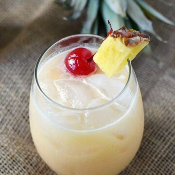 A small glass filled with coconut milk, pineapple juice and rum garnished with a pineapple wedge and cherry.