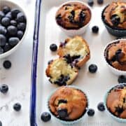 One split and five whole blueberry muffins on a white tray with a bowl of fresh blueberries off to the side and title graphic across the top.