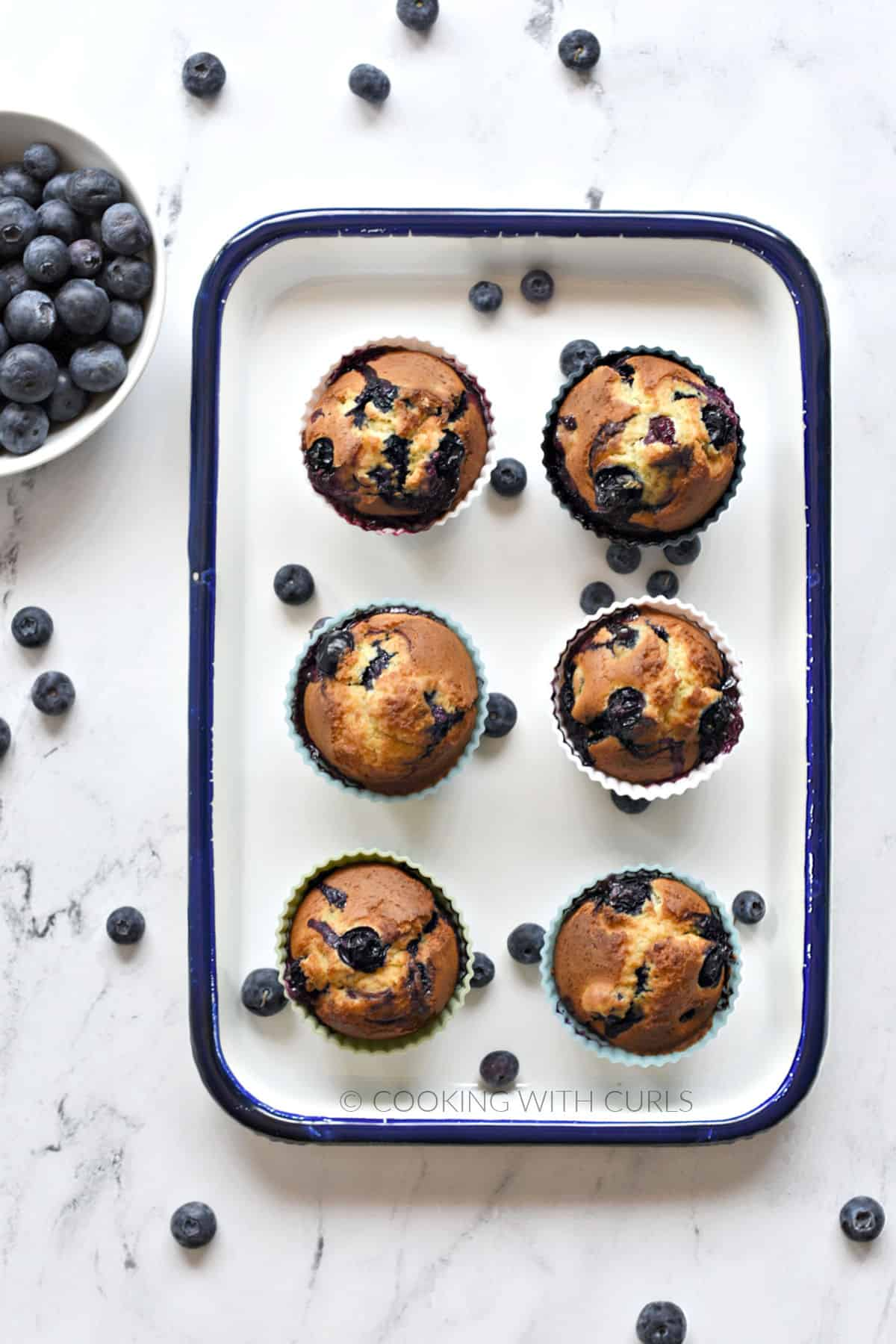 Six blueberry muffins on a white tray with a bowl of fresh blueberries in the upper right corner.