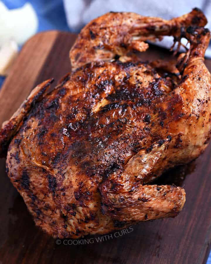 Whole roast chicken on a walnut board sitting on a blue tile background.