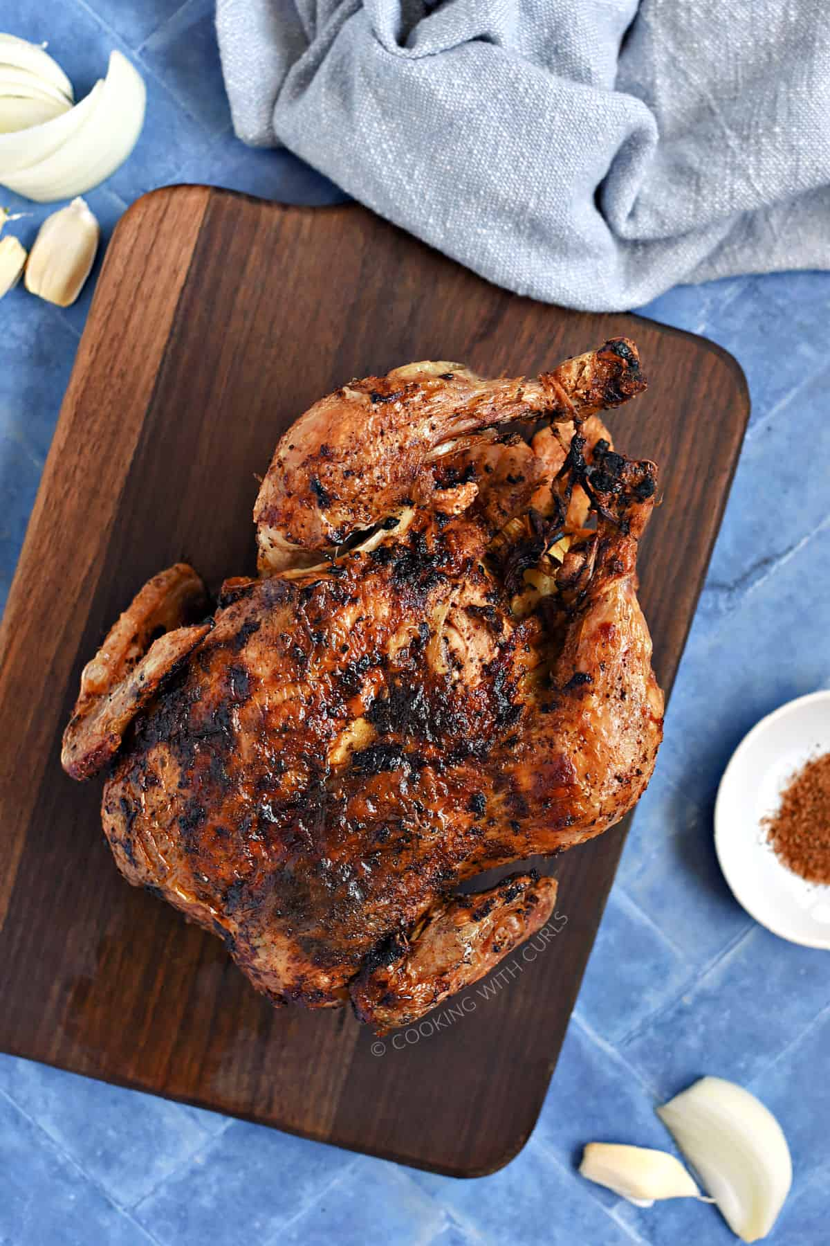Looking down on a whole roast chicken on a walnut board.