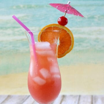 Bright red cocktail in a hurricane glass with an orange slice, cherry, pink paper umbrella, and purple straw.