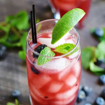 A pink drink in an ice filled glass with fresh blackberries, mint leaves and a lime wedge.