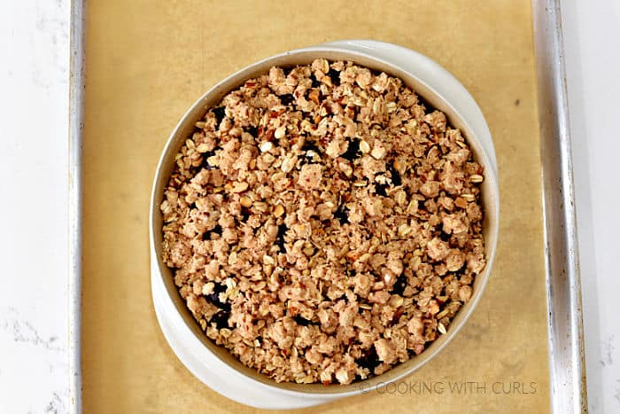 Cherry Almond Crisp in a baking set on a parchment lined baking sheet.