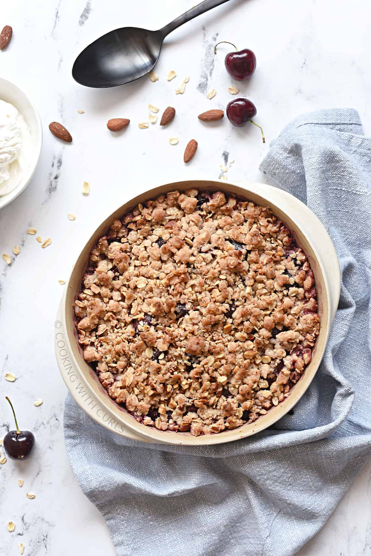 Looking down on a cherry crisp in a round baking dish with a bowl of whipped cream in the upper left corner.