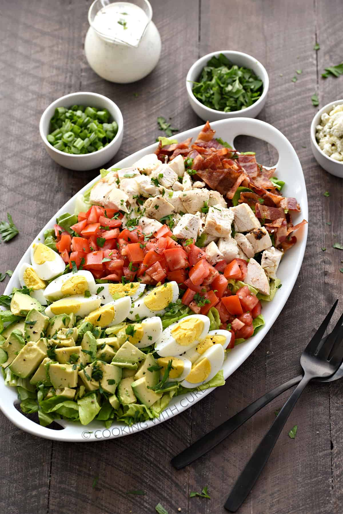 Chopped avocado, hard-boiled eggs, tomatoes, chicken, and bacon on a bed of lettuce with green onions, parsley, crumbled blue cheese, and ranch dressing in the background