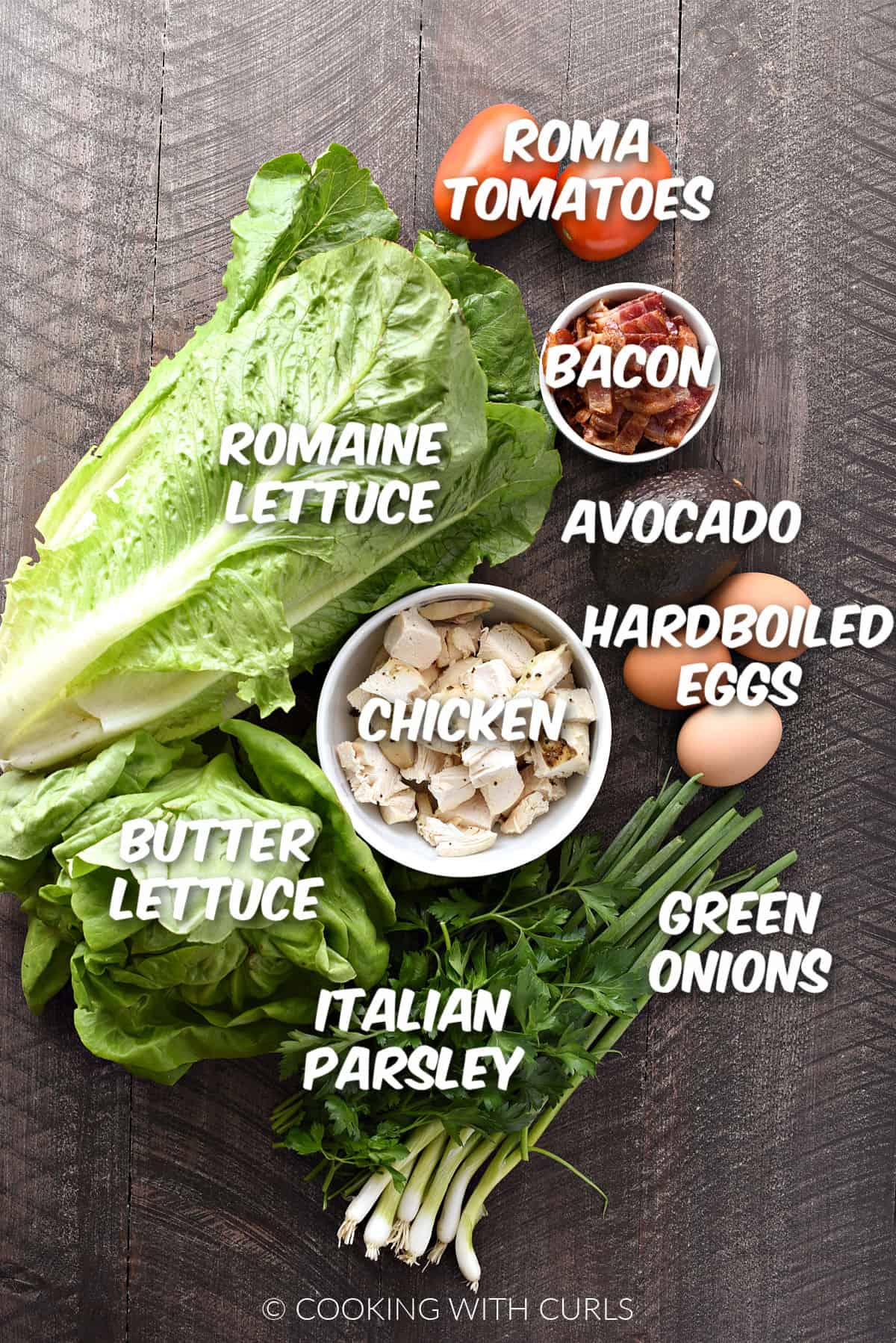A head of romaine and butter lettuces, chopped chicken, two Roma tomatoes, an avocado, three hard boiled eggs, green onions, and Italian parsley.