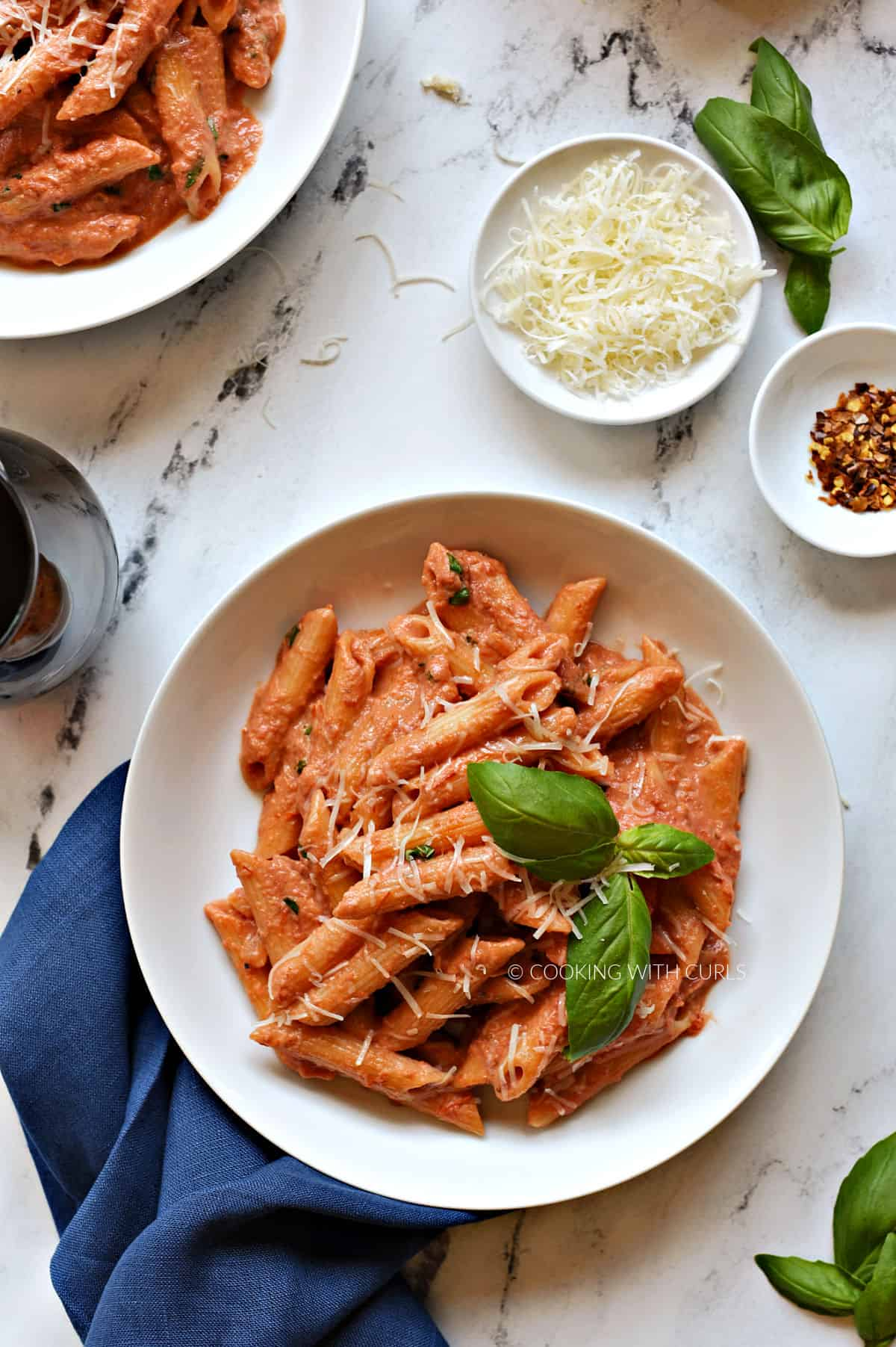 Creamy tomato sauce covered penne pasta garnished with grated cheese and fresh basil in a white bowl.