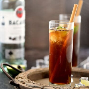Rum and coke in a tall, skinny glass with a lime wedge and bamboo straw, with a second drink in the background.