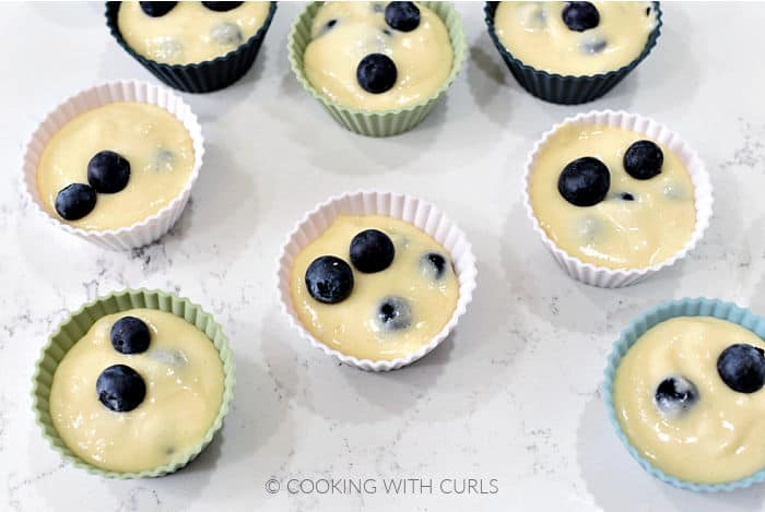 Eight blueberry muffins in silicone baking cups sitting on the counter.