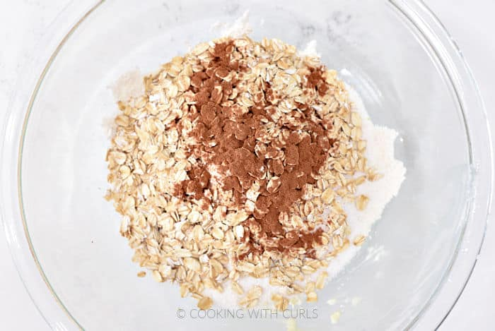 Flour, oats, cinnamon, and sugar in a glass mixing bowl.