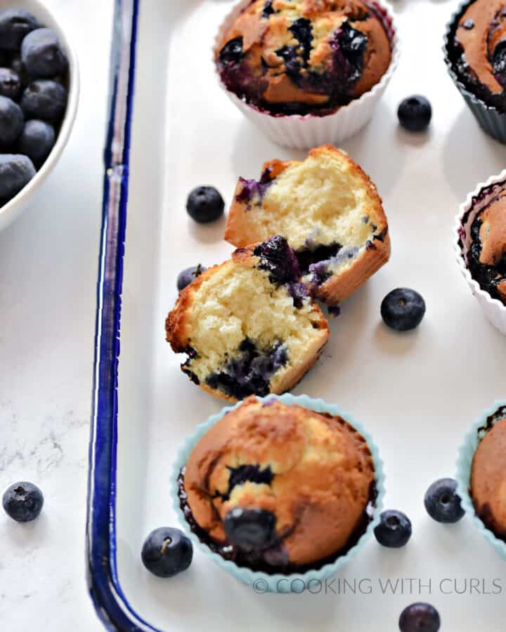 One split and five whole blueberry muffins on a white tray with a bowl of fresh blueberries off to the side.