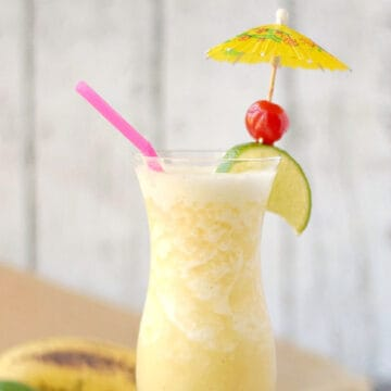 Blended banana cocktail in a hurricane glass with a lime wedge, cherry, yellow paper umbrella, and pink straw.
